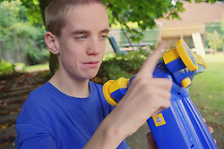 Teenage boy with autism holding plastic toy,