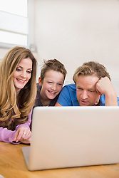Happy family lying on floor looking at laptop