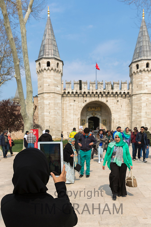 Muslim woman taking photograph with iPad tablet and tourists at Topkapi Palace, Topkapi Sarayi, in Istanbul, Republic of Turkey