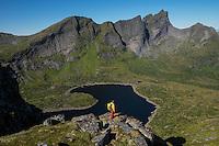 Female hiker overlooking mountain valley from summit of Nonstind mountain peak, Moskenesøy, Lofoten Islands, Norway
