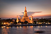"07 MARCH 2009 -- BANGKOK, THAILAND: Sunset at Wat Arun, a Buddhist temple (wat) in the Bangkok Yai district of Bangkok, Thailand, on the west bank of the Chao Phraya River. The full name of the temple is Wat Arunratchawararam Ratchaworamahavihara. The outstanding feature of Wat Arun is its central prang (Khmer-style tower). It may be named ""Temple of the Dawn"" because the first light of morning reflects off the surface of the temple with a pearly iridescence. Steep steps lead to the two terraces. The height is reported by different sources as between 66,80 m and 86 m. The corners are surrounded by 4 smaller satellite prangs. The prangs are decorated by seashells and bits of porcelain which had previously been used as ballast by boats coming to Bangkok from China. The central prang is topped with a seven-pronged trident, referred to by many sources as the ""trident of Shiva"". Around the base of the prangs are various figures of ancient Chinese soldiers and animals. Over the second terrace are four statues of the Hindu god Indra riding on Erawan. The temple was built in the days of Thailand's ancient capital of Ayutthaya and originally known as Wat Makok (The Olive Temple). In the ensuing era when Thonburi was capital, King Taksin changed the name to Wat Chaeng. The later King Rama II. changed the name to Wat Arunratchatharam. He restored the temple and enlarged the central prang. The work was finished by King Rama III. King Rama IV gave the temple the present name Wat Arunratchawararam. As a sign of changing times, Wat Arun officially ordained its first westerner, an American, in 2005. The central prang symbolizes Mount Meru of the Indian cosmology. The satellite prangs are devoted to the wind god Phra Phai. Photo By Jack Kurtz"