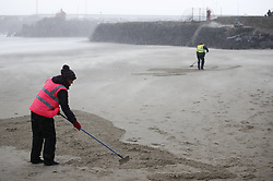 © Licensed to London News Pictures. 11/11/2018. Folkestone, UK. Artists struggle to create a sand portrait of First World War poet Wilfred Owen on the beach at Folkestone, Kent as the weather turns wet and windy at an Armistice Centenary event entitled 'Pages of the Sea'. Portraits are being created by communities on 32 beaches around the UK to say goodbye and thank you, to the millions of men and women who left these shores during the war, many never to return. Lieutenant Wilfred Edward Salter Owen, MC died on 4th November 1918 only days before the Armistice. One of Britain's most celebrated war poets - his short career was directly inspired by the conflict – he composed nearly all his works from August 1917 to September 1918, many published posthumously. Photo credit: Peter Macdiarmid/LNP