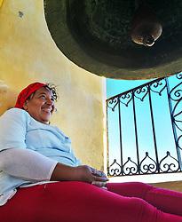 Smiling woman sitting under church bell in Trinidad, Cuba.