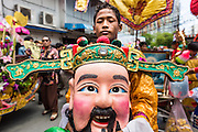 """05 JULY 2014 - BANGKOK, THAILAND:  A man carries a Chinese style head during a parade for vassa in Bangkok. Vassa, called """"phansa"""" in Thai, marks the beginning of the three months long Buddhist rains retreat when monks and novices stay in the temple for periods of intense meditation. Vassa officially starts July 11 but temples across Bangkok are holding events to mark the holiday all week.   PHOTO BY JACK KURTZ"""