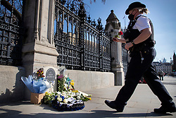 © Licensed to London News Pictures. 22/03/2021. London, UK. A police officer places a rose on the PC Keith Palmer memorial outside the Houses of Parliament. Today marks four years since the Westminster Bridge terror attack and a commemorative plaque is expected to be installed on Westminster Bridge when Coronavirus restrictions are lifted . Photo credit: George Cracknell Wright/LNP
