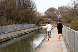 Edinburgh, Scotland, UK. 25 March, 2020. Day two of the Government enforced lockdown in the UK. All shops and restaurants and most workplaces remain closed. Cities are very quiet with vast majority of population staying indoors. Pictured; Two joggers taking their daily exercise alongside the Union Canal at Hermiston in Edinburgh. Iain Masterton/Alamy Live News