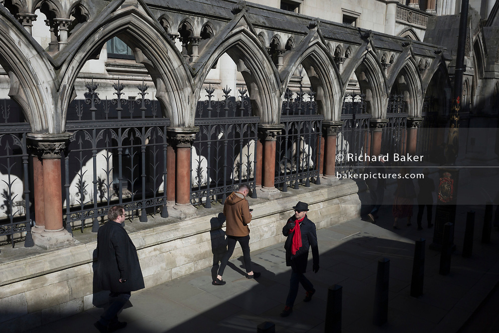 Pedestrians walk beneath the Gothic arches of the Royal Courts of Justice on the Strand, on 11th march 2020, in London, England. Designed by George Edmund Street, who died before it was completed, it is a large grey stone edifice in the Victorian Gothic style built in the 1870s and opened by Queen Victoria in 1882. It is one of the largest courts in Europe.