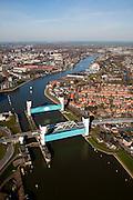 Nederland, Zuid-Holland, Capelle aan den IJssel, 20-03-2009; stormvloedkering in de Hollandsche IJssel. Bij storm en dreigend hoog water wordt een van de twee schuiven naar beneden gelaten, de tweede schuif dient al reserve. De scheepvaart kan de gesloten kering paseren via de naastgelegen schutsluis. Links Capelle a/d IJssel, rechts Krimpen aan den IJssel..De stormvloedkering maakt deel uit van de Deltawerken en is als eerste voltooid in 1958. Ten tijde van De Ramp - watersnood 1953 - werd het zeewater door de storm opgestuwd en dreigde de verzwakte rivierdijken in het achterland het te begeven waardoor grote van het laag gelegen westen van Nederland ondergelopen zouden zijn..Netherlands, Capelle at the river IJssel, near Rotterdam: storm surge barrier, protects the highly populated western part of Holland, which lies below sea level. In case of storm and threat of high water, one of the two doors is lowered into the river (the second door is a spare one). The lock next to the barrier allows shipping when the barrier is closed.Swart collectie, luchtfoto (toeslag); Swart Collection, aerial photo (additional fee required).foto Siebe Swart / photo Siebe Swart