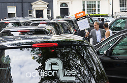 """Mayfair, London, May 24th 2016. Drivers from minicab operator Addison Lee bring traffic to a standstill in Berkely Square, outside of the offices of owner Carlyle Group, in protest against new """"unfair"""" pay rates as the company battles to compete with cut-price Uber, with some drivers claiming they are earning as little as £4.99 per hour. PICTURED: Minicabs sound their horns outside Landsdowne House, where Carlyle Group is headquartered"""