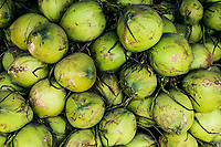 Green coconuts piled high at a streetside market in Koh Samui, Thailand,