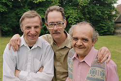 Group of men with learning disabilities standing outside in garden with arms around each other,