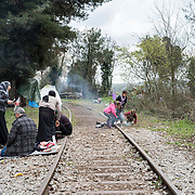 A family sitting next to a disused railway line, near the transit camp of Idomeni, Greece.<br /> <br /> Thousands of refugees are stranded in Idomeni unable to cross the border. The facilities are stretched to the limit and the conditions are appalling.