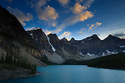 Strong winds blow cumulus clouds over the Canadian Rockies and Moraine Lake at sunset. Moraine Lake, located in Banff National Park, Alberta, Canada, stands at the base of 10 tall mountains, an area called the Valley of the Ten Peaks.