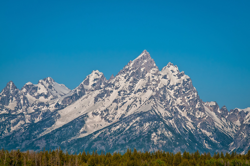 Four of the many peaks in the Grand Tetons, from left to right - Middle Teton, Grand Teton, Mount Owen, and Teewinot. These stunning snowy mountains are found just south of Yellowstone National Park in Wyoming.