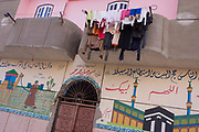 Washing dries from a balcony above an Islamic wall mural in Gezirat, a village on the West Bank of Luxor, Nile Valley, Egypt. The possessions of local Egyptians hang from a washing line above the illustrations depicting Mecca and a man leading a camel through fertile fields. Amidst the bustle of this busy regular event, people from many miles around have come to trade and buy their provisions.
