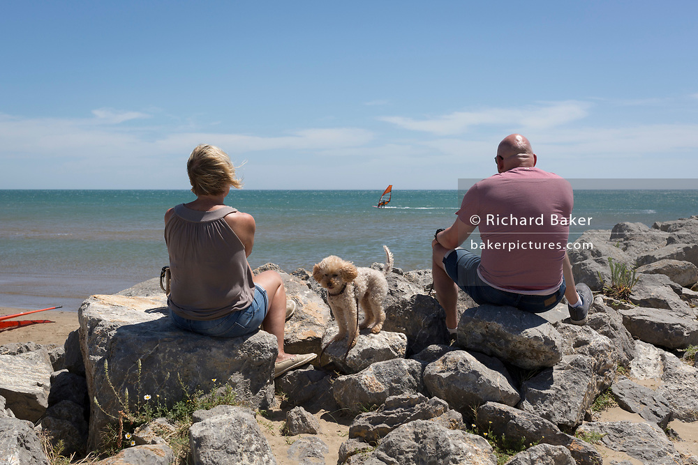 With their pet dog sitting between them, a couple sit on rocks watching windsurfers at the beach overlooking the Mediterranean Sea, on 23rd May, 2017, in Gruisson, Languedoc-Rousillon, south of France