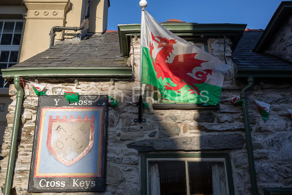 The Welsh Dragon, the national flag of Wales, hangs in evening sunshine outside the the Cross Keys pub, on 12th September 2018, in Dolgellau, Gwynedd, Wales.