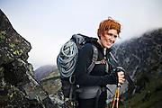 Portrait of Veronika Glukhova carrying a climbing rope to the base of Mount Stuart, Alpine Lakes Wilderness, Washington.