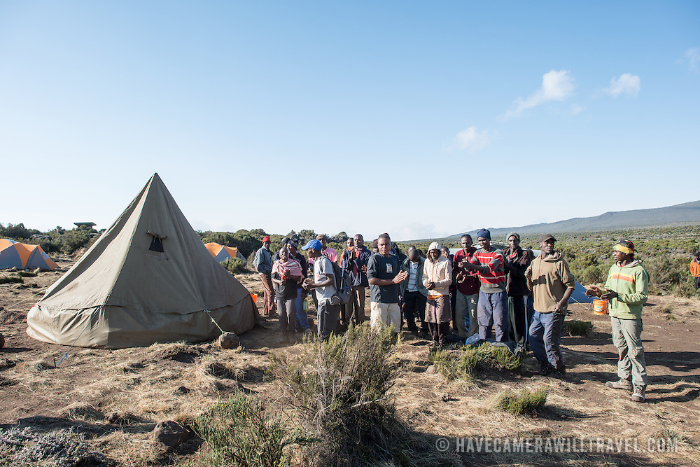 Porters form a welcoming party for their customers at Shira 1 camp on Mt Kilimanjaro.