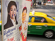 29 JANUARY 2014 - BANGKOK, THAILAND: A taxi passes a defaced campaign sign for the ruling Pheu Thai party on Soi 63 Sukhumvit (Ekkamai) in Bangkok. Thais are supposed to vote Sunday, February 2 in a controversial national election. Anti-government protestors have vowed to disrupt the election. One person was killed and several injured in election related violence during early voting on Sunday Jan. 25. The ruling Pheu Thai party is widely expected to win the election, which is being boycotted by the Democrats and opposition parties.      PHOTO BY JACK KURTZ