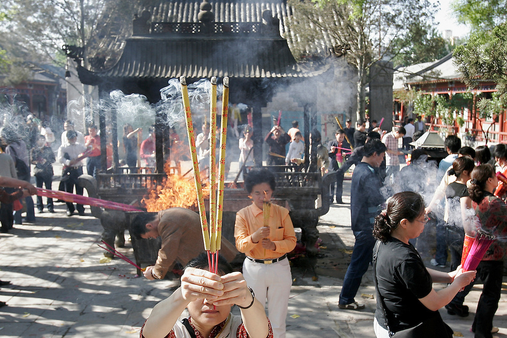 A woman offers her incense towards a Daoist protector on the 15th day of the Lunar month , considered a good day to speak to Gods, at Baiyuguan.  Baiyuguan,called White Cloud Temple in English, is over 1,200 years old and stands the south west of Beijing, China.  White Cloud Temple is the largest Daoist structure in Beijing and home of the Dragon Gate sect of Daoism.