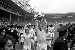Leeds United's Jack Charlton (lifting FA Cup) makes sure he features in the next day's newspapers by posing with the FA Cup during his team's lap of honour