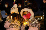 21 DECEMBER 2020 - DES MOINES, IOWA: Children with electric candles at a memorial vigil for the homeless people who have died in Iowa in 2020. More than 100 people gathered on the steps of the State Capitol in Des Moines to honor the homeless who died in Iowa in 2020. The ceremony is held every year on December 21, the longest night of the year. Twenty-five homeless people have died in Iowa so far in 2020.     PHOTO BY JACK KURTZ