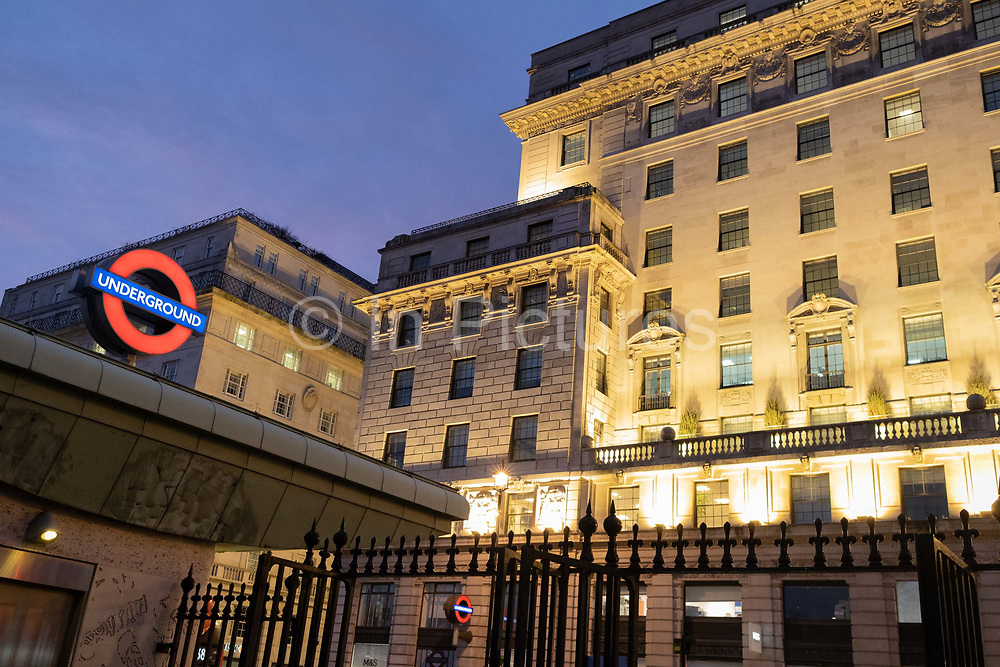 Residential flats and apartments overlook the illuminated roundel of London Undergrounds Green Park tube station and the iron gates of Green Park that leads downhill towards Buckingham Palace, on 3rd February 2021, in London, England.