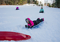Jasmin and Autumn Boisvert enjoy an afternoon of sledding together with their cousins and grandfather at Gilford Outing Club Tuesday.  (Karen Bobotas/for the Laconia Daily Sun)