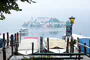 A boat approaches the harbor in Orta San Giulio on Lake Orta with Isola San Giulio in the distance. Piedmont, Italy