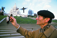 Middle-aged Frenchman with a beret, feeding sparrows from his hand at the base Butte Montmartre with Sacre Coeur Cathedral in the background