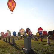 A young girl watches the launch from Battle Creek Memorial Park  as hot air balloons take to the skies around rural Michigan near Battle Creek during the World Hot Air Ballooning Championships. Battle Creek, Michigan, USA. 20th August 2012. Photo Tim Clayton