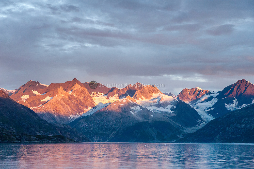 Mountains surrounding the Topeka Glacier catch the first rays of sunlight at dawn in Glacier Bay National Park, Alaska.
