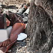 A Syrian refugee sleeps under an olive tree in Kara Tepe camp