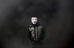 April 13, 2018 - Khan Younis, Gaza Strip, Palestinian Territory - A Palestinian protester wearing an Anonymous mask hurl stones towards Israeli security forces during clashes in a tent city protest where Palestinians demand the right to return to their homeland, at the Israel-Gaza border, in Khan Younis in the southern Gaza Strip. (Credit Image: © Ashraf Amra/APA Images via ZUMA Wire)