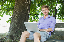 Mid adult man using laptop on bench, smiling