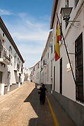 Woman walking along a quiet street in village of Jabugo, Sierra de Aracena, Huelva province, Spain