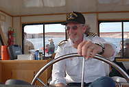 The pilot of the Lake Powell tour boat guides the craft on the way to Rainbow Bridge National Monument.