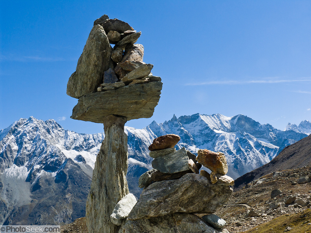 """A rock cairn balances above Arolla village (municipality of Evolène), in Val d'Hérens, Valais (Wallis or Valley) canton, Switzerland, on the High Route (Chamonix-Zermatt Haute Route), Europe. Snow dusts peaks of Les Dents des Veisivi (left) and Les Aiguilles de la Tsa (right) in the Pennine Alps. Published in """"Light Travel: Photography on the Go"""" by Tom Dempsey 2009, 2010."""