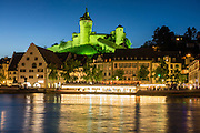 After sunset, Munot Castle is floodlit in green above a cruise boat reflecting in the Rhine River in Schaffhausen, Switzerland, Europe. The popular Untersee Lake-Rhine boat trip from Schaffhausen to Kreuzlingen is nearly 50 km long. Schaffhausen's iconic circular fortress, was built by forced labor in 1564-1589 after the religious wars of the Reformation. A steep stairway climbs from Old Town through vineyards to reach this impressive Renaissance castle. Schaffhausen was founded where trading ships had to set anchor because Rhine Falls blocked further travel.