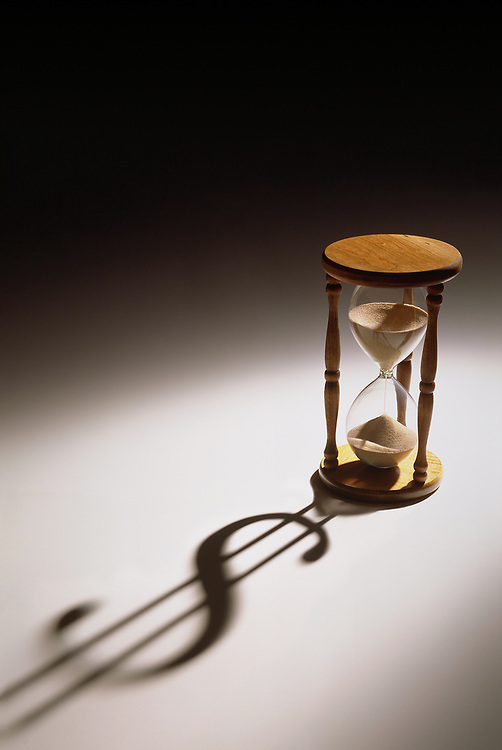 Spotlight on an hourglass with the shadow of a dollar sign being cast onto the table