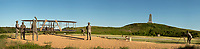 NC01324-00...NORTH CAROLINA - Panoramic image of a sculpture of Orville Wright starting the first successful flight on an airplane on December 17, 1903 at Killl Devil Hills on the Outer Banks at Kitty Hawk and a man with a camera recording the event and other locals cheering him on; now part of the Wright Brothers National Memorial with local residents and a crew from the nearby Lifesaving Station on hand to help.
