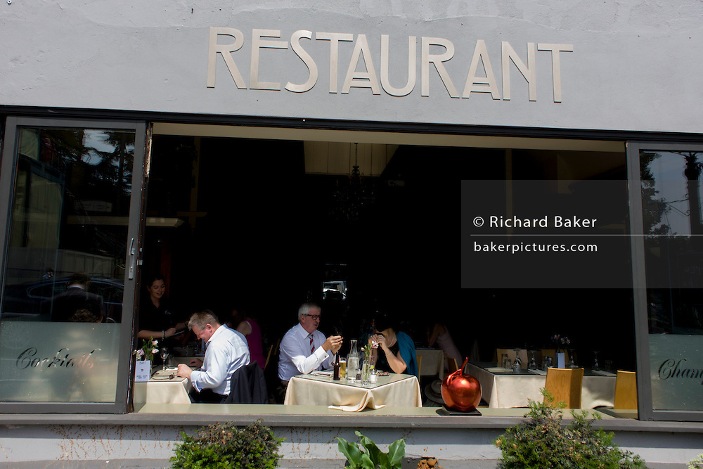 Customers enjoy fresh air in seats of a generic restaurant with its front window open during the annual Royal Ascot horseracing festival in Berkshire, England. Royal Ascot is one of Europe's most famous race meetings, and dates back to 1711. Queen Elizabeth and various members of the British Royal Family attend. Held every June, it's one of the main dates on the English sporting calendar and summer social season. Over 300,000 people make the annual visit to Berkshire during Royal Ascot week, making this Europe's best-attended race meeting with over £3m prize money to be won.