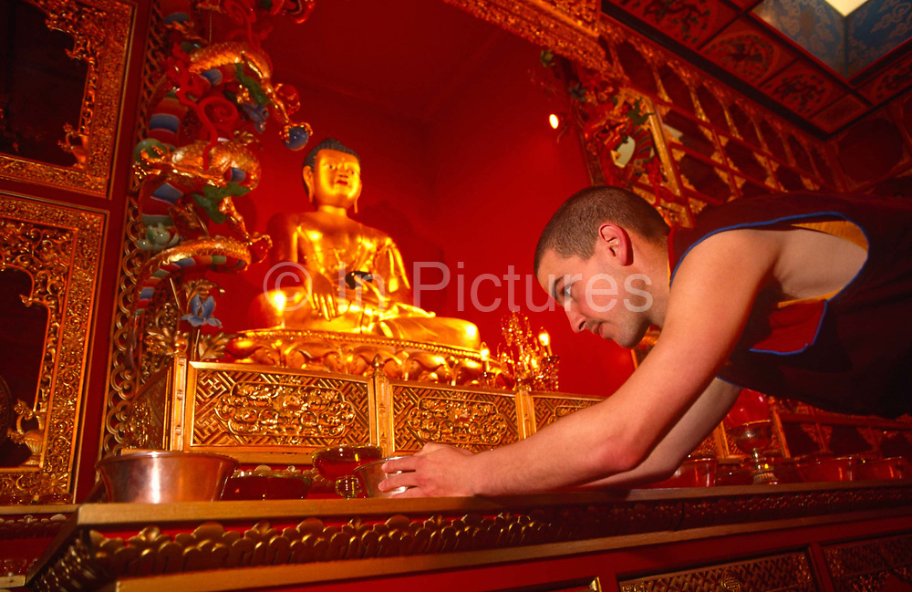 Bending forward as a mark of humility and respect for his deity, a young follower of Tibetan-Buddhism adjusts a prayer bowl in front of an effigy of Buddha at the Kagyu Samye Ling Monastery and Tibetan Centre in Eskdalemuir, Scotland. This young western man wears traditional Tibetan monk's clothes and many here have had a troubled youth, sometimes escaping a criminal past so arrive in the Scottish wilderness for isolated retreats and self-purification, short-term spiritual relaxation or to follow Tibetan teaching methods for discovering inner-peace, through prayer and meditation. This Tibetan Buddhist complex associated with the Kagyu school celebrated its 40th anniversary in 2007.