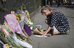 © Licensed to London News Pictures. 05/08/2016. London, UK. A woman places a floral tribute at the spot in Russell Square where American Darlene Horton was killed and five others were injured. A Norwegian man of Somali heritage has been arrested.  Photo credit: Peter Macdiarmid/LNP