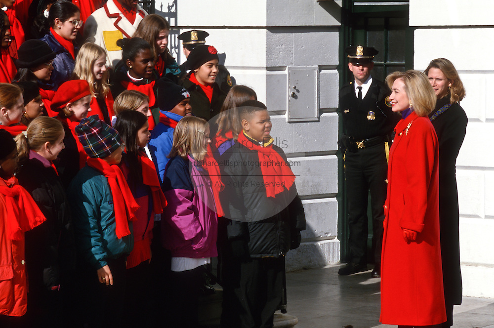 First lady Hillary Clinton greets a children's choir during the arrival of the White House Christmas tree November 27, 1996 in Washington, DC. The National Christmas Tree Association presented Mrs. Clinton with the tree, an 18 1/2-foot Colorado Blue Spruce, grown in Coshocton, Ohio, which will grace the White House Blue Room during the Christmas season.
