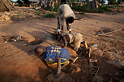 Two boys, controlled by a guard, are looking for impure gold in the last step of the extraction in an artisanal processing site near Bagega, pop. 9000, a large village affected by lead poisoning due to the unsafe techniques employed for extracting gold, in Zamfara State, Nigeria. The contamination is caused by ingestion and breathing of lead particles released in the steps to isolate the gold from other metals. This type of lead is soluble in stomach acid and children under-5 are most affected, as they tend to ingest more through their hands by touching the ground, and are developing symptoms often leading to death or serious disabilities.