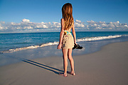 Young girl standing on the beach and looking out at the ocean on Grace Bay, Turks & Caicos