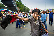 26 MAY 2014 - BANGKOK, THAILAND: A woman taunts riot police during a protest against the coup in Thailand at Victory Monument during a pro-democracy rally in Bangkok. About two thousand people protested against the coup in Bangkok. It was the third straight day of large pro-democracy rallies in the Thai capital as the army continued to tighten its grip on Thai life.   PHOTO BY JACK KURTZ