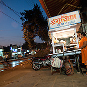Devo Baghel (48. in Orange suit) next to her Gup-chup cart on the street fo Raipur, Chhatisgarh. She  took a Rs 5,000 (EUR 72) loan through the microfinancing program to broaden her small scale business, selling Gup-chup, a savory street food snack on the streets of Raipur. Her weekly payment for the loan is Rs 224 (EUR 3.2).